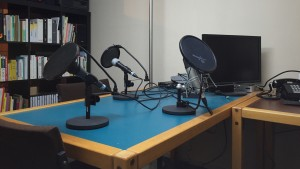 Photo: Three microphones, a computer screen and a telephone on a table in front of a bookshelf.